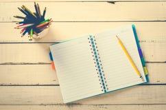 Покрасьте карандаш и тетрадь на деревянной таблице грубой Стоковое Изображение RF