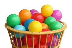Покрасьте пластичные шарики в корзине над белой предпосылкой Стоковые Изображения