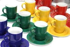 Покрасьте чашки в зеленых, красных, голубых и желтых цветах Стоковые Изображения