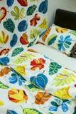 покрасьте чистые одеяла и подушки на кровати Стоковые Фото