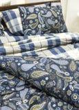 покрасьте чистые одеяла и подушки на кровати Стоковое фото RF