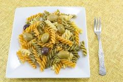 Покрашенная макарон с оливками служила на желтом острословии скатерти Стоковое фото RF