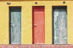 3 покрашенная старая деревянная дверь и желтая стена Стоковое Изображение