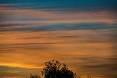 покрашенное конспектом небо захода солнца с облачностями с разрывами Стоковое Изображение