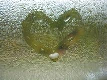 Покрашенное сердце на падениях стекла и дождя окна Стоковая Фотография
