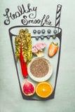 Покрашенное стекло с ингридиентами питья smoothie или вытрезвителя: Семена Chia, апельсин, розовый брокколи, клубники, голубики и Стоковое Фото