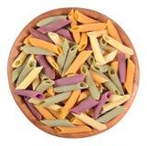Покрашенное сырое итальянское penne макаронных изделий в деревянном шаре на белизне Стоковая Фотография RF