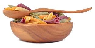 Покрашенное сырое итальянское penne макаронных изделий в деревянном шаре на белизне Стоковое Изображение RF