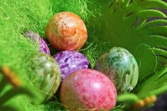 Покрашенное цветастое пасхальное яйцо в зеленой корзине Стоковые Изображения
