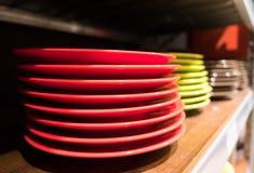 Покрашенные блюда на деревянных книжных полках Стоковая Фотография