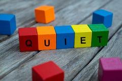 покрашенные деревянные кубы с письмами показано слово тихое, абстрактная иллюстрация стоковое изображение