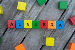 покрашенные деревянные кубы с письмами показано alnusra слова, абстрактная иллюстрация стоковое изображение