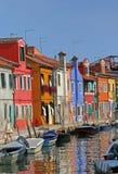 покрашенные дома в острове Burano в Венеции и отражать Стоковое Фото