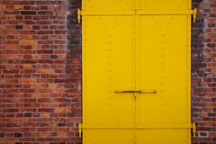 Покрашенные желтым цветом дверь и кирпичная стена металла Стоковые Изображения