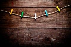 Покрашенные зажимки для белья на веревочке на деревянном столе или доске для backg Стоковые Фотографии RF