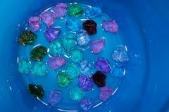 Покрашенные камни на дне голубого ведра, заполненном с водой стоковое изображение