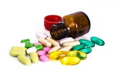 Покрашенные капсулы, пилюльки и медицинская стеклянная бутылка Стоковые Изображения