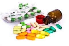 Покрашенные капсулы, пилюльки и медицинская стеклянная бутылка Стоковое Изображение