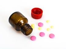 Покрашенные капсулы, пилюльки и медицинская стеклянная бутылка Стоковое Изображение RF