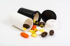 Покрашенные капсулы, таблетки и пилюльки в пластичном опарнике Стоковые Фотографии RF