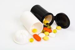 Покрашенные капсулы, таблетки и пилюльки в пластичном опарнике Стоковые Изображения