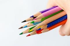 Покрашенные карандаши в руке на белой предпосылке стоковое изображение rf