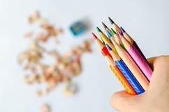 Покрашенные карандаши в руке против запачканных shavings на белом backgr стоковые фото