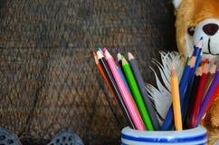 Покрашенные карандаши и кукла медведя на сетчатой предпосылке Стоковая Фотография RF