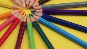 Покрашенные карандаши лежа на яркой желтой предпосылке в круге акции видеоматериалы
