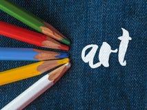 Покрашенные карандаши на джинсовой ткани искусство литерности Стоковое Изображение RF