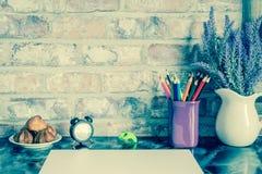 Покрашенные карандаши в кружке, ваза лаванды цветут, хронометрируют, лампа пола, свет ночи, плита тортов, чашка кофе, белая бумаг Стоковая Фотография