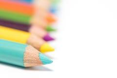 Покрашенные карандаши в расположении на белой предпосылке Стоковые Фотографии RF