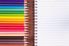 Покрашенные карандаши и пустая тетрадь Стоковая Фотография