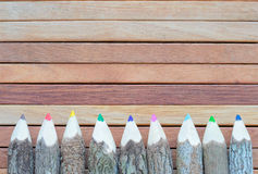 Покрашенные карандаши на деревянной предпосылке Рука делает карандаш цвета Стоковое Фото
