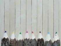 Покрашенные карандаши на деревянной предпосылке Рука делает карандаш цвета Стоковые Фотографии RF