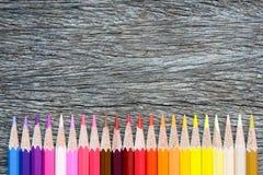 Покрашенные карандаши на деревянной предпосылке Рука делает карандаш цвета Стоковое Изображение RF