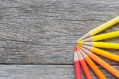 Покрашенные карандаши на деревянной предпосылке Рука делает карандаш цвета Стоковая Фотография RF