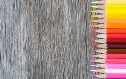 Покрашенные карандаши на деревянной предпосылке Рука делает карандаш цвета Стоковые Изображения
