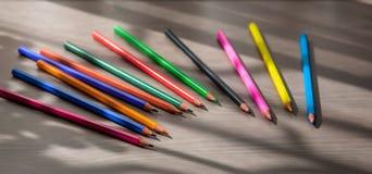 Покрашенные карандаши на таблице Стоковые Изображения
