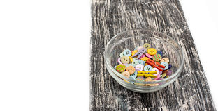 Покрашенные кнопки в стеклянной чашке на старой деревянной доске Стоковое Фото