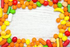 Покрашенные конфеты на древесине Стоковое Фото