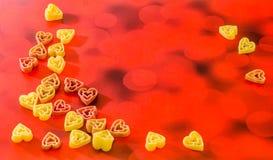 Покрашенные (красный цвет, желтеет апельсин) макаронные изделия формы сердца, покрашенная предпосылка bokeh degradee, конец вверх Стоковые Фотографии RF