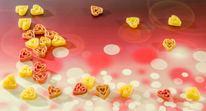Покрашенные (красный цвет, желтеет апельсин) макаронные изделия формы сердца, покрашенная предпосылка bokeh degradee, конец вверх Стоковая Фотография