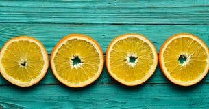Покрашенные куски апельсина на предпосылке бирюзы деревянной Взгляд сверху Стоковое Фото