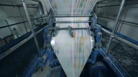 Покрашенные листы газеты двигая на транспортер оформления, офис печатания сток-видео