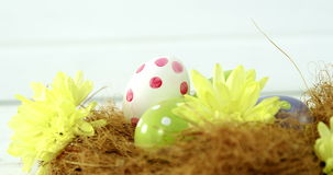 Покрашенные пасхальные яйца в гнезде на деревянной поверхности сток-видео