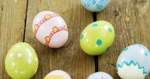 Покрашенные пасхальные яйца в гнезде на деревянной поверхности видеоматериал