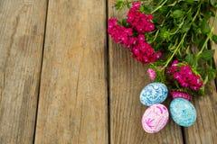 Покрашенные пасхальные яйца и пук цветка на деревянной предпосылке Стоковая Фотография RF