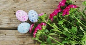 Покрашенные пасхальные яйца и пук цветка на деревянной предпосылке видеоматериал