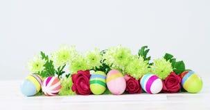 Покрашенные пасхальные яйца, пук цветка и конверт на деревянной предпосылке видеоматериал